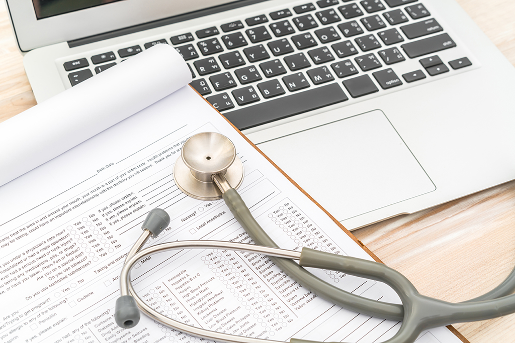Stethoscope and prescription on laptop.